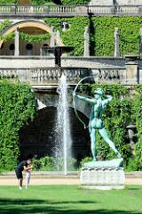 Gartenanlage mit Bronzeskulptur Bogenschütze vor dem Orangerieschloss im Potsdamer Park Sanssouci.