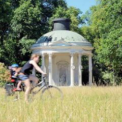 Fahrradfahrerin mit Kind, hohes Gras auf der Wiese vor dem Rundtempel im Potsdamer Park Sanssouci - der Freundschaftstempel ist ein kleiner Rundtempel, den der preußische König Friedrich II. zum Andenken an seine 1758 verstorbene Lieblingsschwester,