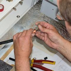 Die Bootselektrik wird  montiert - Elektrokabeln im Innenraum des Daysailers - Bootselektriker bei der Arbeit in der Kajüte.