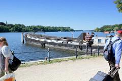 Binnenschiff am Ufer der Havel, Templiner See in Potsdam - Fussgänger auf der Promenade,