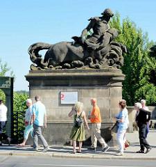 Dekorelement - Figur auf dem Brückenpfosten an der Berliner Seite der Glienicker Brücke; Tafel  zur Geschichte der Brücke auf der Berliner Seite; Touristen gehen vorbei.