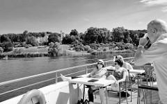 Blick vom Ausflugsboot über die Havel, Tiefer See zum Babelsberger Park - zwischen Bäumen das denkmalgeschützte Schloss Babelsberg in Potsdam. Seit 1990 gehört der Park Babelsberg  zum UNESCO Welterbe.