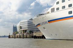 Das Kreuzfahrtschiff EUROPA liegt am Hamburger Kreuzfahrtterminal Hafencity - im Hintergrund Unilevergebäude mit Café am Wasser.