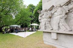 Kriegsklotz am Dammtordamm in Hamburg - im Hintergrund die Veranstaltung zum Baubeginn des Deserteurdenkmals.