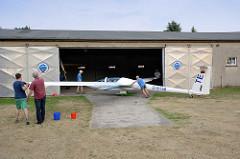 Das Segelflugzeug wird in die Flugzeughalle auf dem Kyritzer Segelflugplatz geschoben.