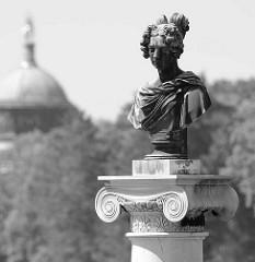 Bronzebüste auf einer Säule am Schloss Charlottenhof Park Sanssuci / Potsdam - im Hintergrund die Kuppel vom Neuen Palais.