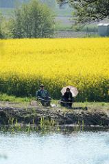 Angler am Fluss Jeetzel in Dannenberg - im Hintergrund blühender Raps, gelbes Rapsfeld.