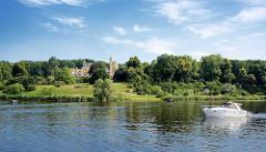 Schlosspark Babelsberg an der Havel / Tiefer See; ein weisses Motorboot, Sportboot fährt havelaufwärts - zwischen Bäumen das Schloss Babelsberg. Seit 1990 gehört der Park Babelsberg als Teil der Schlösser und Parks von Potsdam und Berlin zu Liste des