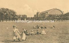 Wiese mit spielenden Kindern vor dem Gebäude des Dammtorbahnhofs in Hamburg Rotherbaum.
