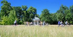 Fahrradfahrer auf dem Fahrradweg durch den Park Sanssouci, hohes Gras auf der Wiese vor dem Pavillon  Park Sanssouci in Potsdam - der Freundschaftstempel ist ein kleiner Rundtempel, den der preußische König Friedrich II. zum Andenken an seine 1758 ve