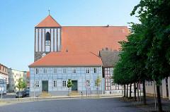 Kirche von Wusterhausen - die Pfarrkirche St. Peter und Paul ist ursprünglich eine spätromanische Basilika von etwa 1229. In mehreren Bauabschnitten wurde sie bis 1479 zur dreischiffigen gotischen gewölbten Hallenkirche erweitert. Im Vordergrund ein