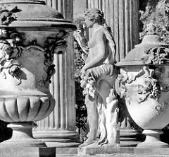 Deckelvasen mit Dekor - Skulptur zwischen kannelierten Säulen im Park Sanssouci von Potsdam.