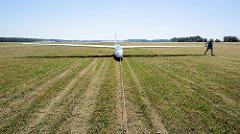 Der Doppelsitzer DG 1001 wird auf dem Kyritzer Segelflugplatz nach der Landung mit dem Flugzeuschlepper zur Startbahn gezogen.