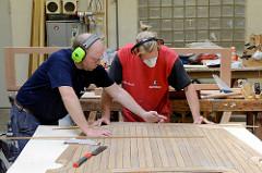 Die Kanten des Mahagonie-Decks werden in der Werkstatt mit Massivholzleisten versehen.