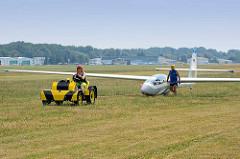 Ein gelandetes Segelflugzeug wird mit dem Flugzeugschlepper wieder zur Startposition gebracht.