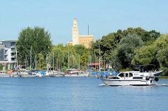 Blick über den Havellauf in Potsdam - Sportboot in Fahrt, Marina; Turm vom Persiusspeicher - 1843 in spätklassizistischen Stil mit Turmzinnen nach Entwürfen von Ludwig Persius errichtet.