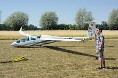 Windenstart eines Segelflugzeugs auf dem Verkehrslandeplatz Kyritz; ein Vereinsmitglied hält beim Start den Gleitflieger in der Waage.
