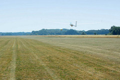 Windenstart eines Segelflugzeugs auf dem Verkehrslandeplatz Kyritz. Beim Start mit der Winde wird das Seil  auf einer Windentrommel aufgerollt, das Segelflugzeug wird auf etwa 90–130 km/h beschleunigt