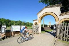 Eingang mit Holztoren, Holzgitter zum Park Sanssouci, Potsdam - Schilder mit Parkordnung und Kasten für freiwillige Spenden - Fahrradfahrer Richtung Linnéstrasse.