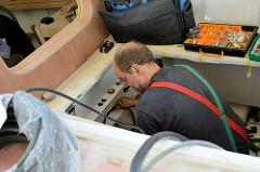 Verlegen von Elektrokabeln im Innenraum des Daysailers - Bootselektriker bei der Arbeit in der Kajüte.