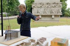 Der Hamburger Künstler  Volker Lang beschreibt das Modell des Deserteurdenkmal, das am Dammtordamm in der Neustadt Hamburgs gebaut werden soll - im Hintergrund der Kriegsklotz / Kriegerdenkmal des Hamburger 76. Infanterieregiments.