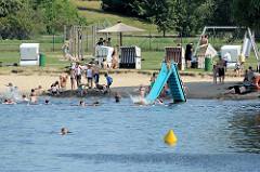 Strandbad Babelsberg am Ufer der Havel / Tiefer See; badende Menschen, Strandkörbe und Wasserrutsche.
