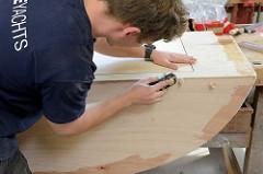 Werkstattarbeiten für den Innenausbau des Daysailors - mit einem Handhobel wird eine Kante bündig gehobelt.