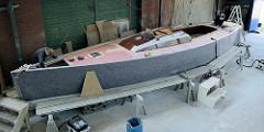Arbeiten am Rumpf des Daysailers - die Bordwand ist mit einer Filzmatte geschützt.