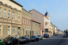 Blick in die Berliner Strasse von Zehdenick - Wohnhäuser mit grauem Rauhputz, parkende Autos.