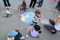 Grillfest von AnwohnerInnen und Flüchtlingen im Hamburger Karoviertel; Kinder malen mit Kreide auf dem Platz.