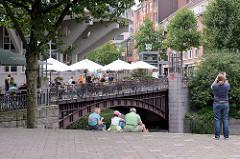 Tische und Sonnenschirme auf der Michaelisbrücke über das Herrengrabenfleet in der Hamburger Neustadt - Touristen sitzen auf der Treppe zum Fleet.
