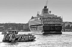 Das Kreuzfahrtschiff Mein Schiff 1 auf der Elbe vor Hamburg - eine Hafenfähre passiert das Heck des Passagierschiffs.