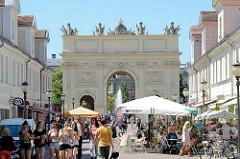 Fussgängerzone Brandenburger Strasse in Potsdam - Touristen schlendern in der Sonne, Strassencafés und Restaurants - im Hintergrund das historische Brandenburger Tor. das Tor wurde 1771 fertiggestellt.