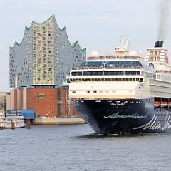 Das Kreuzfahrtschiff, Passagierschiff MEIN SCHIFF 1 verlässt Hamburg - lks. die Elbphilharmonie in der Hafencity.