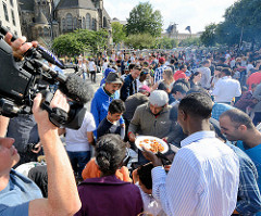 Grillfest von AnwohnerInnen und Flüchtlingen im Hamburger Karoviertel. Dicht gedrängt stehen die Menschen um die Grillplätze - ein Kameramann nimmt die Szene auf.