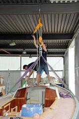 Wiegen des Daysailors auf der Werft -  der Rumpf des Segelschiffes wird mit Gurten an eine Kranwaage / Industriewaage gehängt.