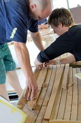 Das Mahagoniedeck des Daysailers wird angefertigt - die Massivholzleisten werden eingepasst.