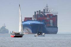 Schiffsverkehr auf der Elbe bei Hamburg - ein Containerfrachter fährt elbaufwärts Richtung Hamburger Hafen - Segelboote unter Segel oder Motor passieren den Frachter.
