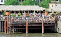 Beach Club an der Elbe bei den Hamburger St. Pauli Landungsbrücken - Strand Pauli; Gäste sitzen in Liegestühlen und blicken auf das Wasser.