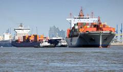 Containerschiffe auf der Elbe im Hamburger Hafen - im Hintergrund das Gebäude der Elbphilharmonie.