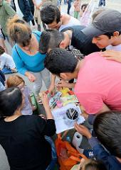 Grillfest von AnwohnerInnen und Flüchtlingen im Hamburger Karoviertel auf dem Tschaikowsky-Platz - Kinderschminken mit Erwachsenen.