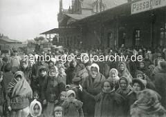 Frauen und Kinder mit Kopftuch und Decken vor den Auswandererhallen auf der Hamburger Veddel. Im Hintergrund ein hochbeladener Pferdewagen mit Gepäckstücken.
