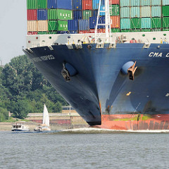 Bug des Containerschiffs CMA CGM AMERIGO VESPUCCI auf der Elbe beim Auslaufen aus dem Hamburger Hafen - kleine Sportboot überholen den Containerfachter.