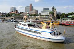 Das Fahrgastschiff Störtebeker vor den St. Pauli Landungsbrücken mit Fahrgästen an Bord - im Hintergrund die Skyline von Hamburg St. Pauli.