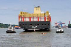 Das Frachtschiff MSC ZOE läuft in den Hafen Hamburgs ein - zwei Schlepper am Heck des Riesenschiffs, kleines Tuckerboot / Sportboot folgt dem Frachter.