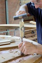 Mit einem Stechbeitel / Stemmeisen werden die Mahagonieleisten der Decksbeplankung eingepasst.