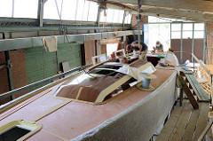 Arbeiten am Deck des Segelschiffs - die Bordwand ist zum Schutz mit Filzmatten abgedeckt.