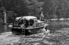 Motorboot in Fahrt nach der Schleusung in der Schleuse von Zehdenick; Gegenlichtaufnahme, Schwarz-Weiß.