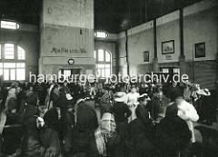 Auswanderer in Hamburg - Veddeler Auswanderhallen; medizinische Untersuchung vor der Abfahrt - an der Wand steht Albert Ballins Wahlspruch Mein Feld ist die Welt.