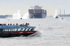 Der Containerfrachter MSC ZOE läuft zum ersten Mal den Hamburger Hafen an - Löschboote auf der Elbe mit Wasserfontäne, eine Hafenfähre kreuzt das Fahrwasser.